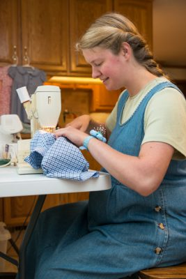 Anna Marie sewing matching outfits so they can be ready for the baby photo session.
